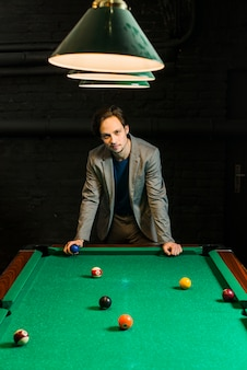 Hombre joven en traje de pie detrás de la piscina de billar sosteniendo la bola en el club