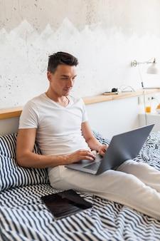 Hombre joven en traje de pijama casual sentado en la cama en la mañana trabajando en la computadora portátil, autónomo ocupado en casa