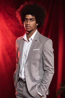 Hombre joven en un traje sobre un fondo de cortina roja