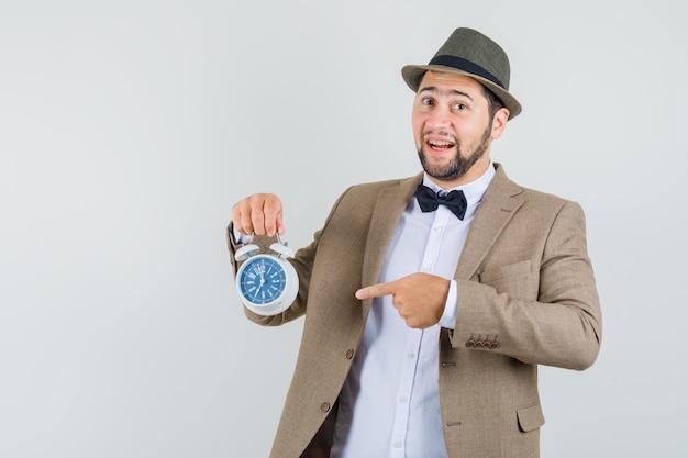 Hombre joven en traje, sombrero apuntando al despertador y mirando alegre, vista frontal.