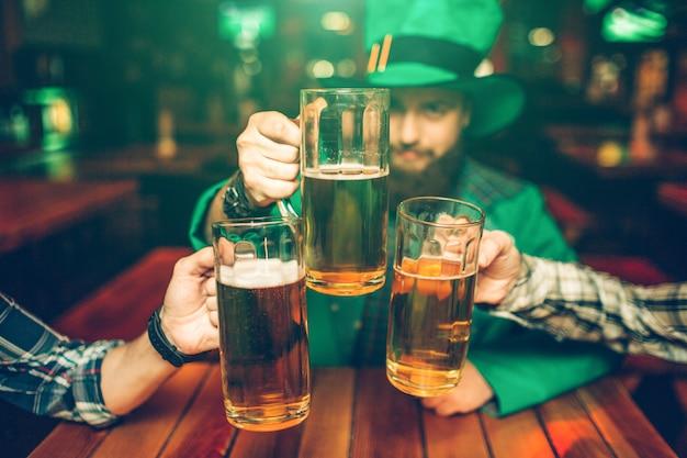 El hombre joven en traje verde se sienta a la mesa con los amigos en pub y sostiene las jarras de cerveza juntas. el esta concentrado.