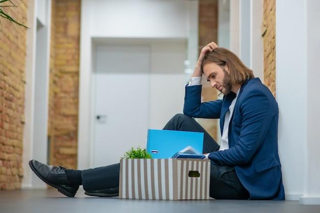Hombre joven triste pensativo en traje de negocios sentado en el piso en un pasillo de oficina cerca de caja con cosas