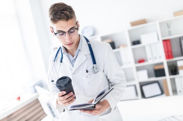Un hombre joven con una túnica blanca de pie en la oficina y sosteniendo un vaso de café y un cuaderno.