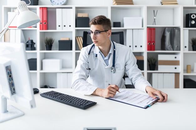 Un hombre joven con una túnica blanca sentado en una mesa en la oficina. sostiene un bolígrafo en la mano y mira el monitor.