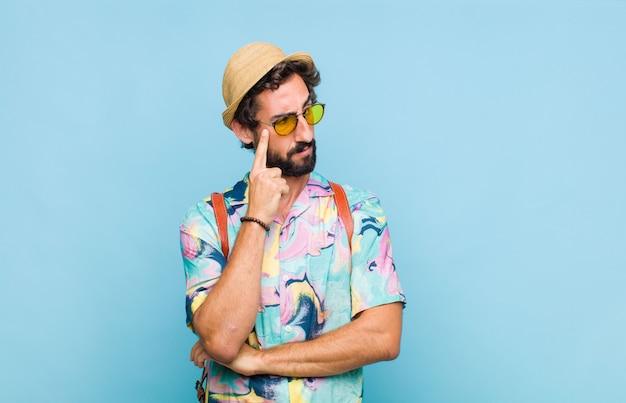 Hombre joven turista barbudo con una mirada concentrada, preguntándose con una expresión dudosa, mirando hacia arriba y hacia un lado