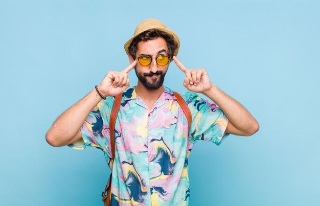 Hombre joven turista barbudo que parece concentrado y pensando mucho en una idea, imaginando una solución a un desafío o problema