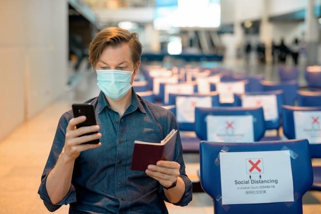 Hombre joven turista con máscara comprobando el teléfono y el pasaporte mientras está sentado con distancia en el aeropuerto