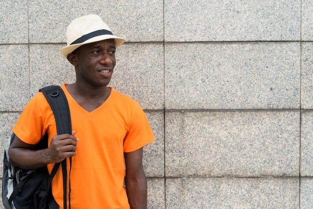 Hombre joven turista con mochila mientras piensa y mira a distancia contra la pared de bloques de hormigón