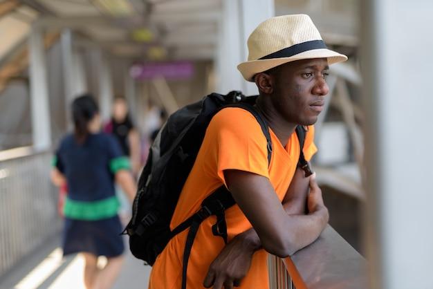 Hombre joven turista pensando mientras mira a la pasarela de la estación de metro en bangkok, tailandia