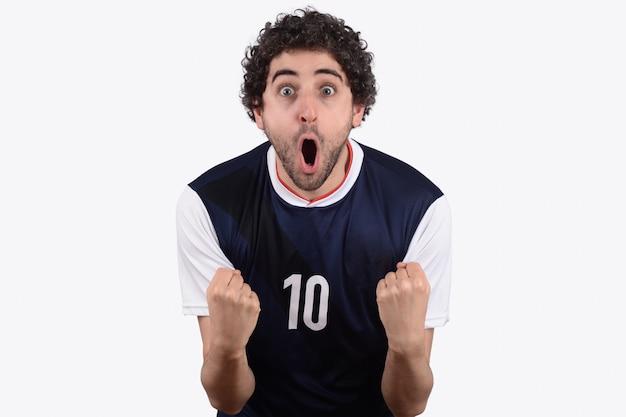 Hombre joven en uniforme del balompié del fútbol que grita mientras que su equipo gana.