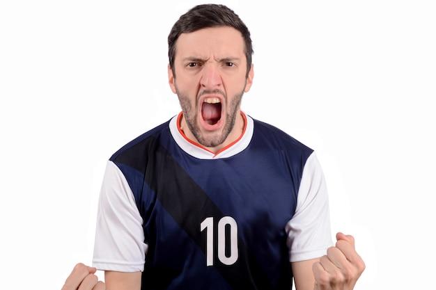 Hombre joven en uniforme del fútbol del fútbol que grita mientras que su equipo gana.