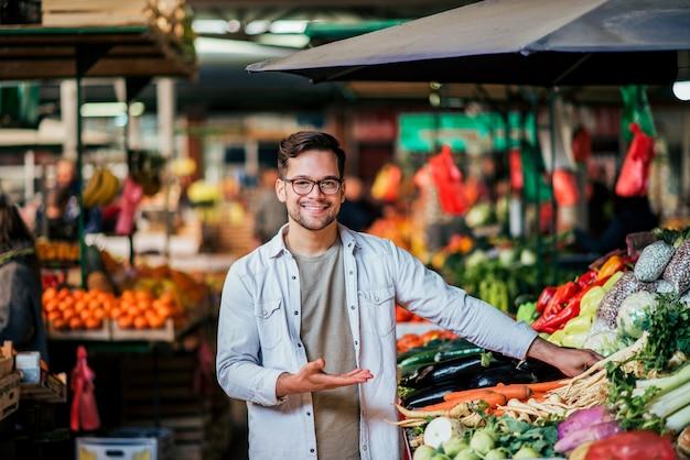 Hombre joven del vendedor en el mercado del granjero.