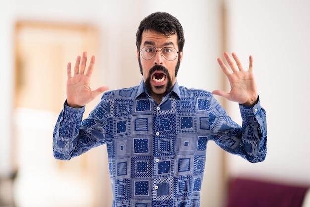 Hombre joven de la vendimia que hace gesto de la sorpresa en fondo unfocused