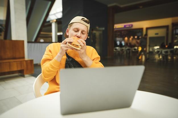 Hombre joven con un vestido casual sentado en una mesa en un restaurante de comida rápida