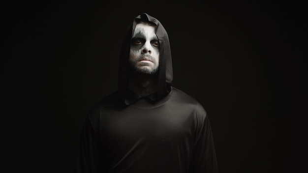 Hombre joven vestido como parca sobre fondo negro en la decoración del tema de halloween
