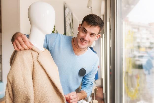 Hombre joven vestido de maniquí en abrigo beige en el escaparate
