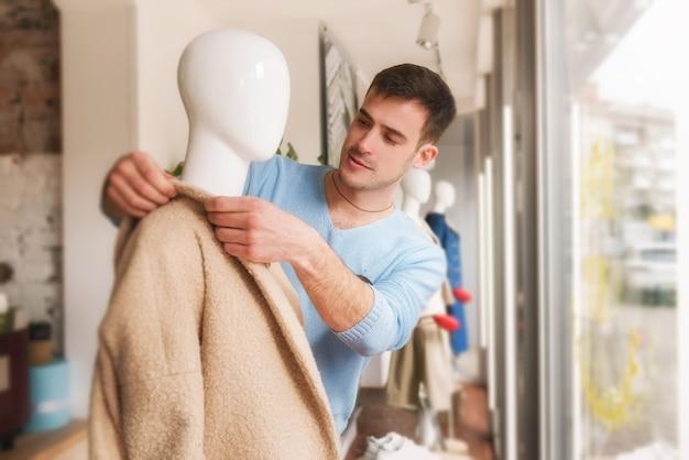 Hombre joven vestido de maniquí en abrigo beige en tienda de ropa
