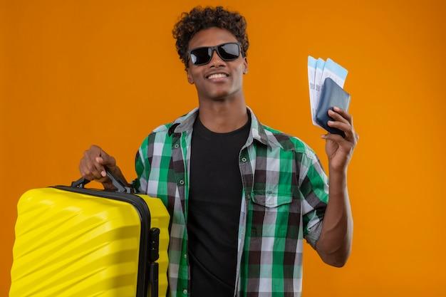 Hombre joven viajero afroamericano con gafas de sol negras de pie con maleta sosteniendo billetes de avión sonriendo alegremente positivo y feliz sobre fondo naranja