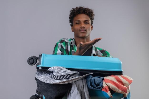 Hombre joven viajero afroamericano con maleta llena de ropa mirando a la cámara que sopla un beso con la mano en el aire siendo encantador