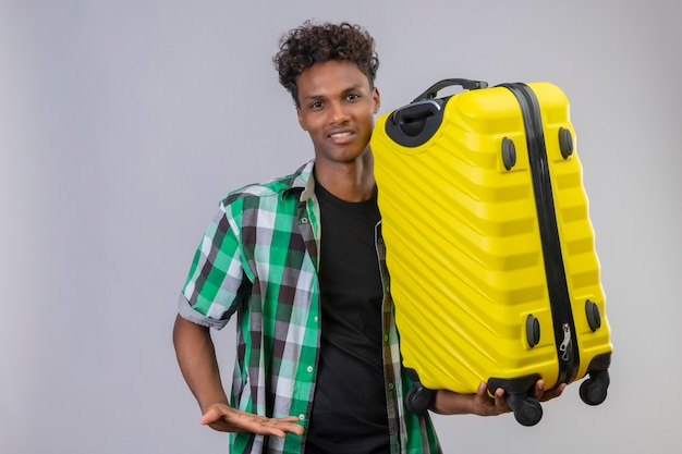 Hombre joven viajero afroamericano con maleta sonriendo alegremente, positivo y feliz