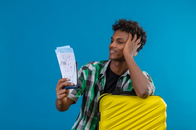 Hombre joven viajero afroamericano con maleta sosteniendo billetes de avión mirándolos con sonrisa de confianza en la cara, satisfecho