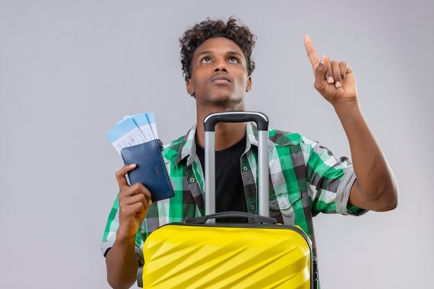 Hombre joven viajero afroamericano de pie con maleta sosteniendo boletos de avión mirando hacia arriba y apuntando con el dedo hacia arriba con cara seria sobre fondo blanco.