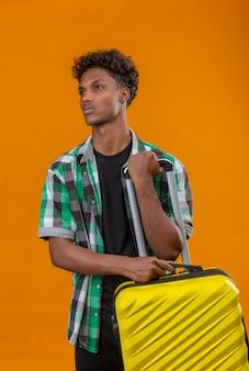 Hombre joven viajero afroamericano que sostiene la maleta mirando a un lado con expresión seria de confianza en la cara