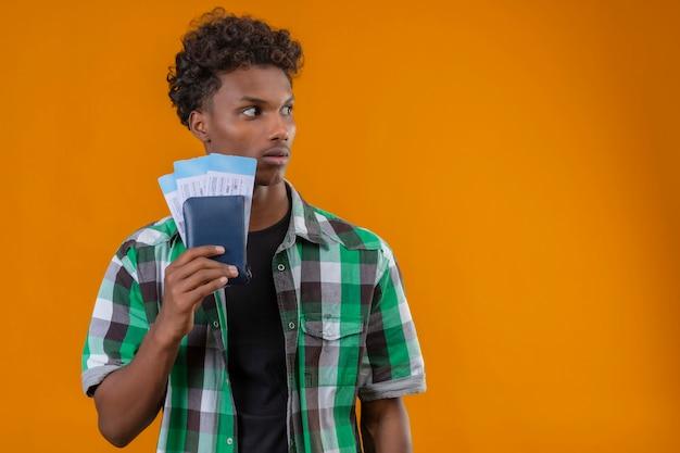 Hombre joven viajero afroamericano sosteniendo billetes de avión mirando a un lado con expresión de miedo en la cara de pie sobre fondo naranja