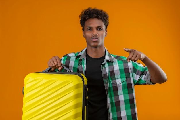 Hombre joven viajero afroamericano sosteniendo la maleta apuntando con el dedo a la cámara mirando confiado y satisfecho