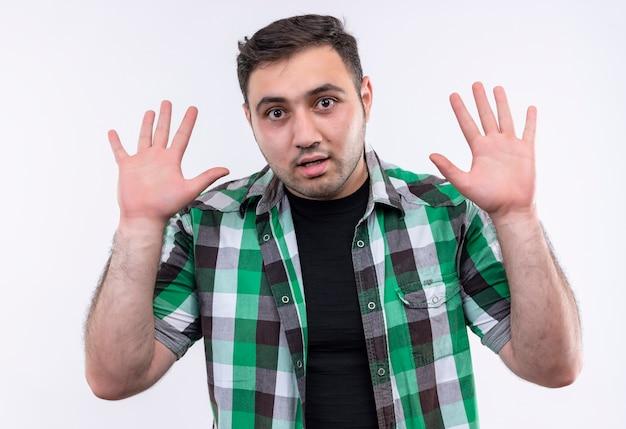 Hombre joven viajero en camisa a cuadros levantando las palmas en señal de rendición, mirando sorprendido de pie sobre la pared blanca
