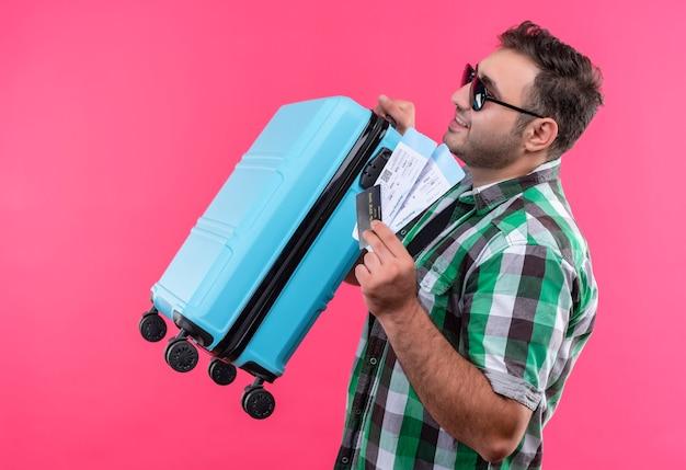 Hombre joven viajero en camisa a cuadros con maleta y billetes de avión de pie de lado sonriendo confiado sobre la pared rosa