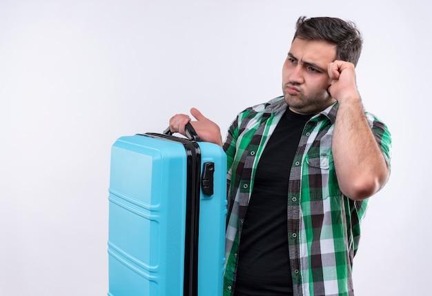 Hombre joven viajero en camisa a cuadros sosteniendo la maleta mirando a un lado confundido y muy ansioso de pie sobre la pared blanca