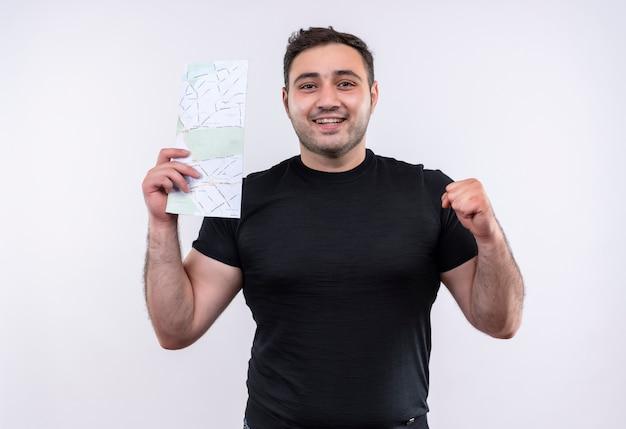 Hombre joven viajero en camiseta negra con billetes de avión feliz y positivo puño sonriendo de pie sobre la pared blanca