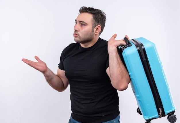 Hombre joven viajero en camiseta negra con maleta mirando a un lado confundido y muy ansioso de pie sobre la pared blanca