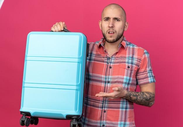 Hombre joven viajero descontento sosteniendo y apuntando a la maleta aislada en la pared rosa con espacio de copia