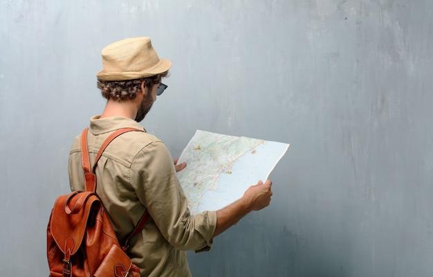 Hombre joven viajero con un mapa y bolso de piel.