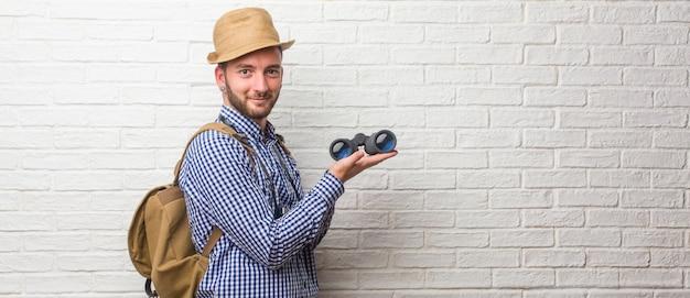 Hombre joven viajero con mochila y una cámara vintage que invita a venir, confiado y sonriente haciendo un gesto con la mano, siendo positivo y amigable. sosteniendo unos prismáticos.