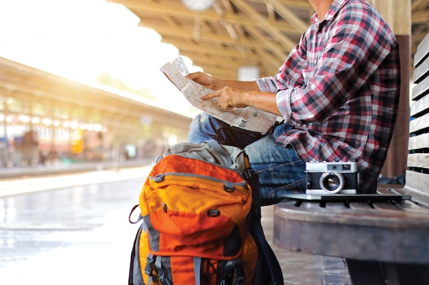 Hombre joven viajero mochilero sosteniendo un mapa en la estación de tren