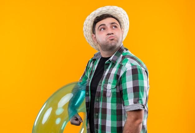 Hombre joven viajero molesto en camisa a cuadros y sombrero de verano sosteniendo un anillo inflable mirando a un lado soplando mejillas de pie sobre la pared naranja