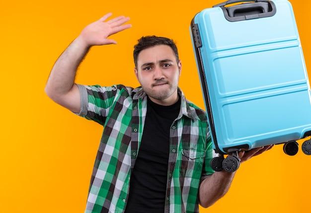 Hombre joven viajero molesto en camisa a cuadros sosteniendo maleta saludando con expresión molesta de pie sobre la pared naranja
