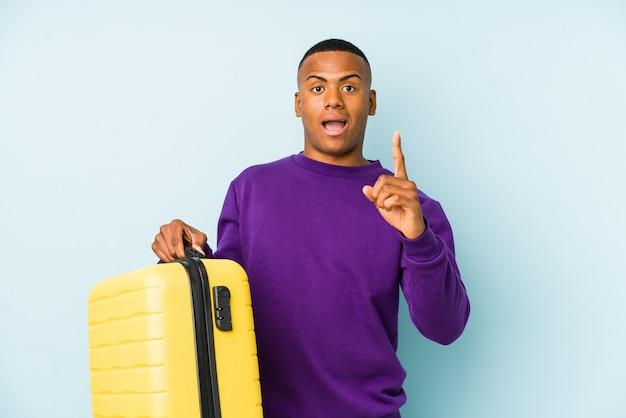 Hombre joven viajero sosteniendo una maleta aislada teniendo una idea, concepto de inspiración.