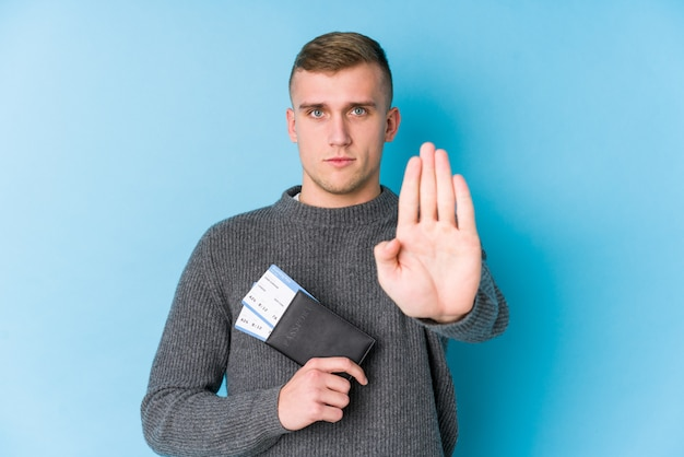 Hombre joven viajero sosteniendo una tarjeta de embarque de pie con la mano extendida que muestra la señal de stop, impidiéndole.