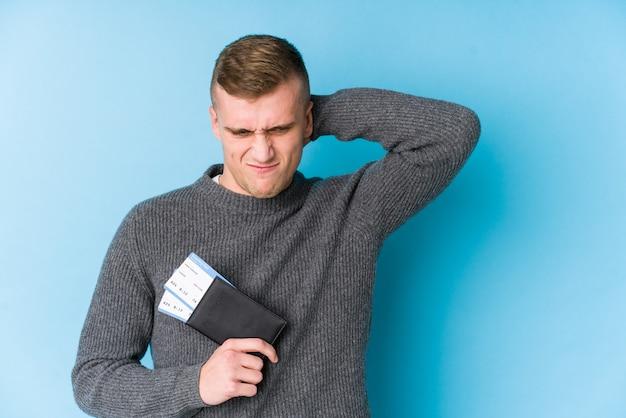Hombre joven viajero sosteniendo una tarjeta de embarque tocando la parte posterior de la cabeza, pensando y tomando una decisión.