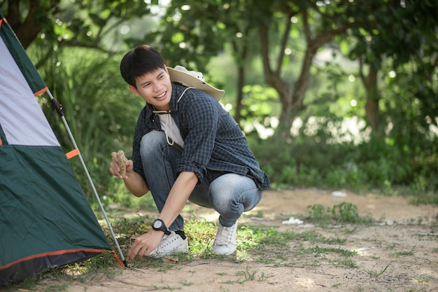 Hombre joven viajero usa una piedra para golpear las clavijas de la tienda en el bosque durante el viaje de campamento en las vacaciones de verano