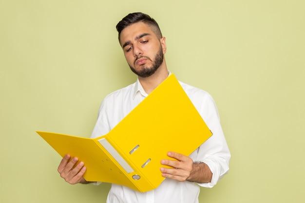 Un hombre joven de vista frontal con camisa blanca sosteniendo archivos amarillos y leyéndolo