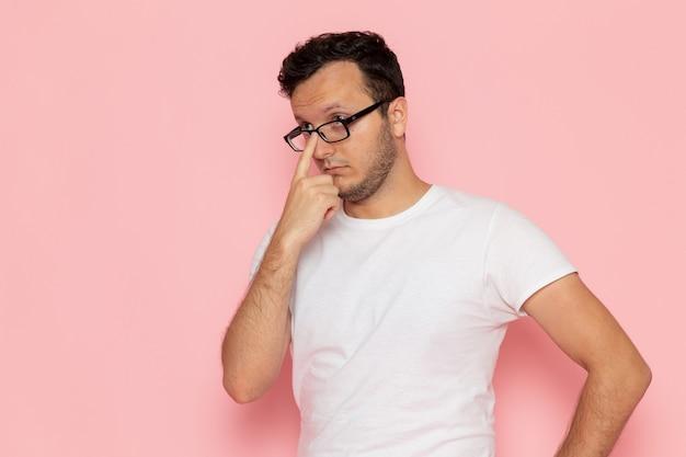 Un hombre joven de vista frontal en camiseta blanca con gafas de sol ópticas en el escritorio rosa hombre color emoción pose