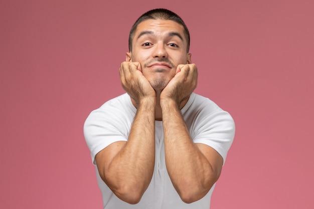 Hombre joven de vista frontal en camiseta blanca posando con expresión curiosa sobre fondo rosa