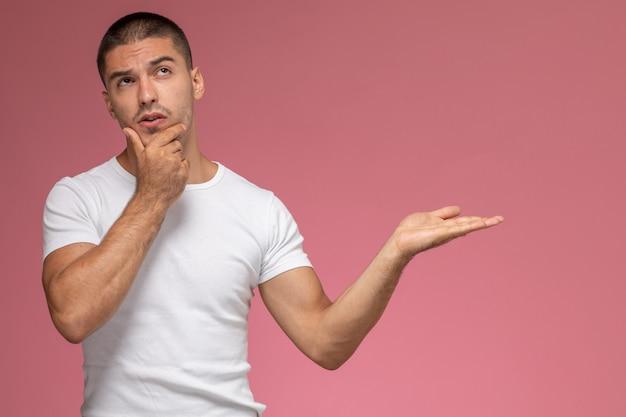 Hombre joven de vista frontal en camiseta blanca posando con expresión de pensamiento sobre fondo rosa
