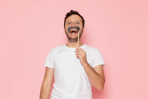 Un hombre joven de vista frontal en camiseta blanca posando y sosteniendo el bigote