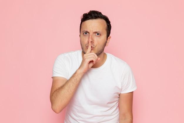 Un hombre joven de vista frontal en camiseta blanca showign signo de silencio